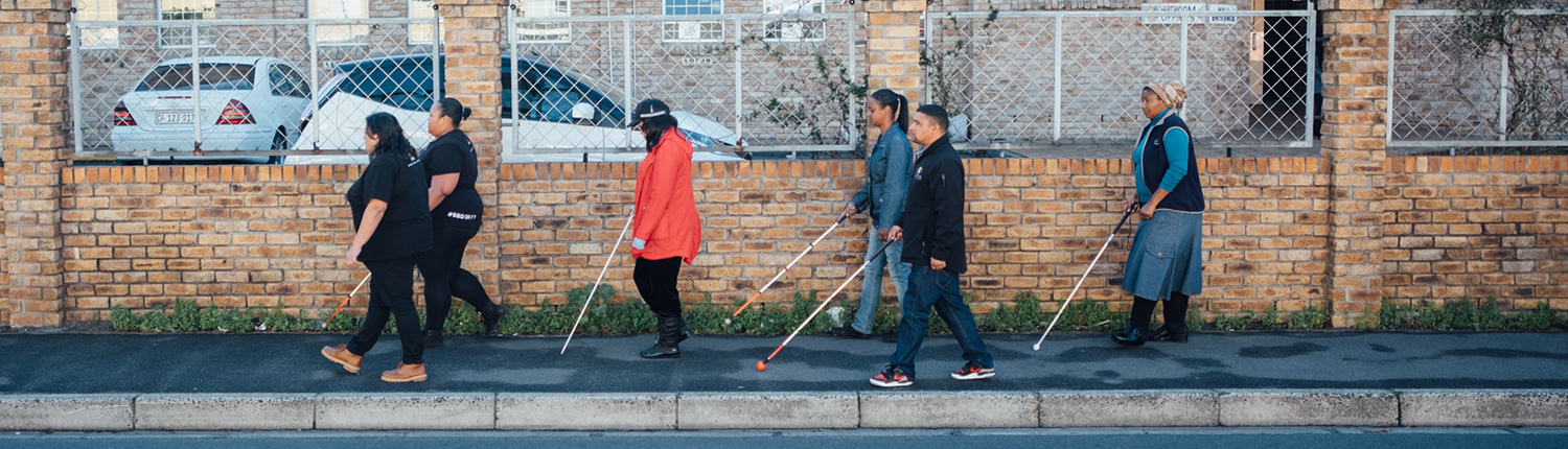 LOFOB clients walk using canes on a sidewalk