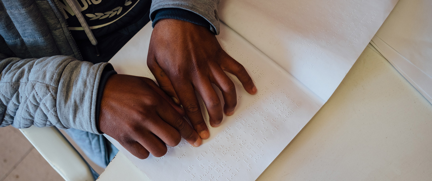 Hands of a learner reading braille